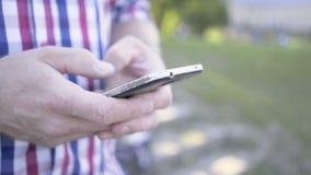 Slutet upp på man` s räcker att bläddra smartphonen glidareskott arkivfilmer