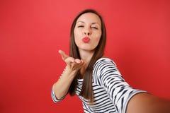Slutet upp selfieskott av den nätta unga kvinnan i tillfällig randig kläder som blåser kyssar, överför luftkyssen som isoleras på fotografering för bildbyråer