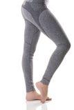 Slutet upp sidosikt av kvinnan lägger benen på ryggen sträcka musklerna av foten i termisk underkläder för gråa sportar med model Arkivbild