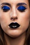 Slutet upp ståenden av bärande blått för kvinnan utgör med svarta kanter Royaltyfri Fotografi