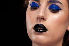 Slutet upp ståenden av bärande blått för kvinnan utgör med svarta kanter Arkivfoto