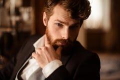Slutet upp ståenden av den säkra affärsmannen har det tjocka ljust rödbrun skägget och mustaschen som formellt kläs och att vara  arkivbild