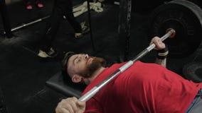 Slutet upp ståenden av en koncentrerad skäggig sportman som gör squatting, övar med skivstången i crossfitmitt stock video