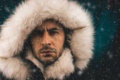 Slutet upp ståenden av en vit man klädde med ett eskimo omslag i snön royaltyfri fotografi
