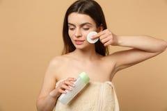 Slutet upp 20-tal för kvinna för brunetthalva naken med perfekt hud som tar bort nakenstudie, utgör isolerat på beige pastellfärg royaltyfri bild