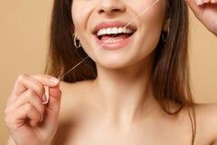 Slutet upp 20-tal för kvinna för brunetthalva naken med perfekt hudnakenstudie utgör genom att använda floss som isoleras på den  royaltyfria bilder