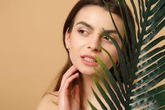 Slutet upp 20-tal för kvinnan för brunetthalvan den nakna med perfekt hud, nakenstudie utgör palmbladet som isoleras på den beige royaltyfri bild