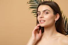 Slutet upp 20-tal för kvinnan för brunetthalvan den nakna med perfekt hud, nakenstudie utgör palmbladet som isoleras på den beige arkivfoto
