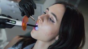 Slutet upp tandläkarehänder behandlar tålmodiga tänder med special utrustning, ultrarapid lager videofilmer