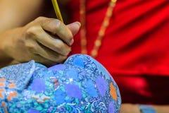 Slutet upp thailändsk kvinnakonstnär i röd thailändsk stilpåklädd målar Royaltyfri Bild