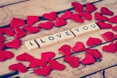 Slutet upp trätext för ÄLSKAR JAG DIG och röd hjärta på wood backgr Royaltyfri Fotografi