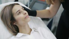 Slutet upp ung kvinna visar kosmetologområden på hennes framsida för injektion och behandling arkivfilmer