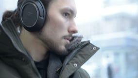 Slutet upp ung lång haired skäggig man för stående i ett omslag och en stor hörlurar sitter offentligt transport vid spårvagnen f stock video