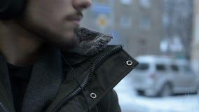 Slutet upp ung lång haired skäggig man för stående i ett omslag och en stor hörlurar sitter offentligt transport vid spårvagnen f lager videofilmer