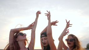 Slutet vänder mot upp flickvänner, sommaraftonen, lyckliga bästa vän som dansar i solnedgång på stranden, tre kvinnliga lönelyfta arkivfilmer