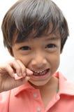 Slutligen första för mjölktänder tandlösa pojkeleende ut Arkivfoto