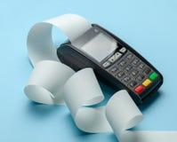 Slutligt kassaapparatmaskinpos. för betalningar och långt rullkassaband på blå bakgrund arkivfoton