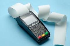 Slutligt kassaapparatmaskinpos. f?r betalningar och l?ngt rullkassaband p? bl? bakgrund royaltyfria bilder