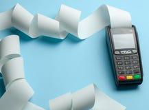 Slutligt kassaapparatmaskinpos. f?r betalningar och l?ngt rullkassaband p? bl? bakgrund Kopiera utrymme f?r text arkivbild
