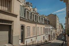 Slutta gatan av Montmartre med halv-fristående byggnader i en solig dag för sen eftermiddag på Paris Royaltyfri Foto