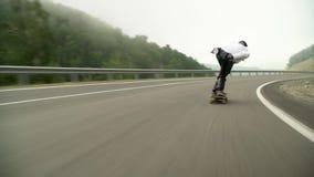 Sluttande longboard i bergen i dimman i morgonen stock video