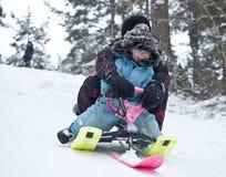 Sluttande på en snowpulka Royaltyfria Bilder