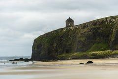 Sluttande strand och Mussenden tempel som är nordlig - Irland kustlinje Royaltyfri Foto