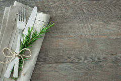 Slverware with an empty tag. Silverware with a twig of rosemary and empty tag on rustic wooden background Stock Images