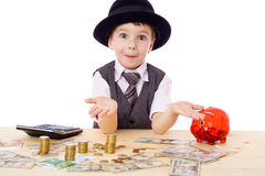 Sly boy at the table with money. Sly boy in black hat with empty hands at the table with pile of money, isolated on white Stock Image