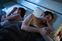 Sly boyfriend using mobile in bed Royalty Free Stock Photo