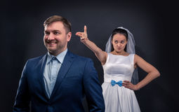 Sly bride brought a finger gun at her groom Royalty Free Stock Images