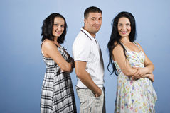 Sly guy with two beautiful women. Sly  and conceited guy in the middle of two beautiful brunette  women  posing in modern clothes isolated on blue background Stock Image