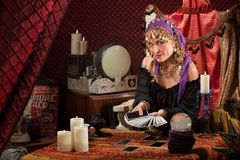 Sly Lady with Tarot Cards. Smiling gypsy soothsayer with hand of tarot cards Stock Image