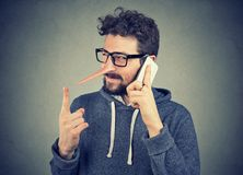 Sly liar man with long nose talking on mobile phone Royalty Free Stock Photo