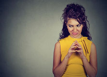 Sly scheming young woman plotting something looking sideways Royalty Free Stock Photography