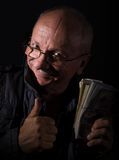 Sly senior man holding dollar bills Royalty Free Stock Photo