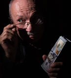 Sly senior man holding dollar bills Stock Image