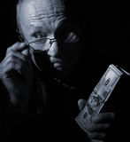 Sly senior man holding dollar bills Royalty Free Stock Image