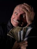 Sly senior man holding dollar bills Stock Photos