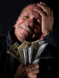 Sly senior man holding dollar bills Royalty Free Stock Photos