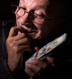 Sly senior man holding dollar bills Stock Photo