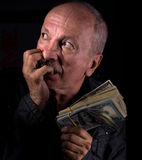 Sly senior man holding dollar bills Royalty Free Stock Photography
