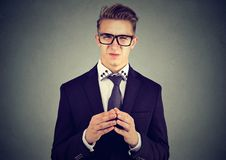Sly business man in glasses looking with disgust at camera. Sly young business man in glasses looking at camera with disgust Royalty Free Stock Photo