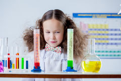Slyly smiling girl posing with colorful test-tubes Stock Image