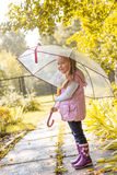 Slyly smiling girl posing under umbrella in park Royalty Free Stock Photos