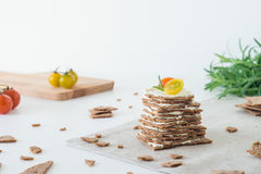 Smällare för frasigt bröd för råg som svenska staplas i form av kakan i lager med mjuk ost, körsbärsröda tomater och rosmarin Arkivfoton
