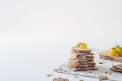 Smällare för frasigt bröd för råg som svenska staplas i form av kakan i lager med mjuk ost, körsbärsröda tomater och rosmarin Royaltyfri Bild