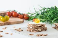 Smällare för frasigt bröd för råg som svenska staplas i form av kakan i lager med mjuk ost, körsbärsröda tomater och rosmarin Royaltyfri Foto