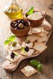Smällare med mjuk ost och oliv ny grated sund tomat för aptitretareost Arkivfoto