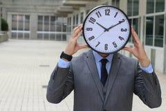 Smälld i arbetare som rymmer tiden främst av hans framsida royaltyfri fotografi